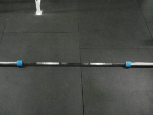 A standard barbell on a matted gym floor with blue duct tape on both ends of the collars.