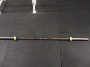 A standard barbell on a matted gym floor with green duct tape on both ends of the collars.