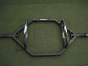 A picture of a large Trap Bar from Rogue on the turf floor of a gym.