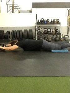 Laura Monroe in a fully extended position performing an Ab Wheel from the knees.