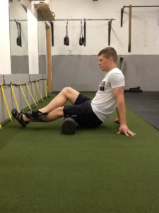 Dickie White rolling his left hamstring on a Foam Roller.