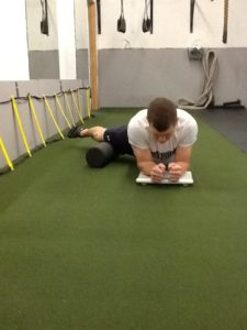 Dickie White rolling his right Adductor with his forearms on a scale.