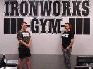 Picture of co-owners Laura Monroe and Dickie White standing in front of an Ironworks Gym logo. Ironworks Gym is located in Binghamton, NY.