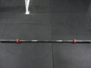 A standard barbell on a matted gym floor with red duct tape on both ends of the collars.