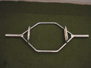 A picture of a standard sized Trap Bar on the turf floor of a gym.