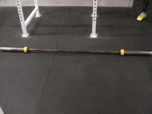 A standard barbell on a matted gym floor with yellow duct tape on both ends of the collars.