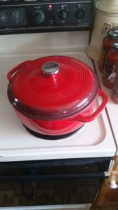 A red dutch oven on a stove.