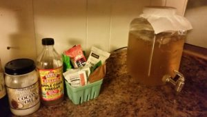 Kombucha brewing in a clear glass jar next to coconut oil and apple cider vinegar.