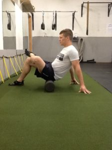 Dickie White rolling his left Glute on a Foam Roller with his left leg cross over his right leg.