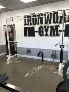 Cable Crossover in front of a painting of the Ironworks Gym logo.