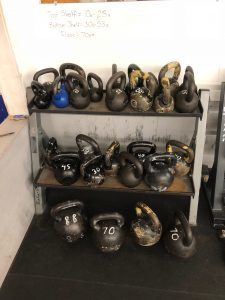 A 2 tier rack of Kettlebells in a variety of sizes and weights